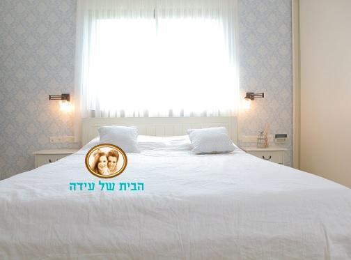 חדר שינה בעיצובנו, טפט מדליונים בתכלת על קיר גב מיטה